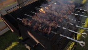 Cocinando kebab en los pinchos en una barbacoa asan a la parrilla almacen de video