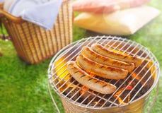 Cocinando la carne, Bratwurst, en un Bbq del verano Fotos de archivo