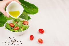 Cocinando la ensalada sana cruda de dieta - flujo del aceite de oliva abajo en la ensalada verde fresca con los tomates en cuenco Imágenes de archivo libres de regalías