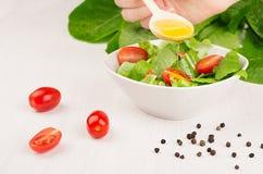 Cocinando la ensalada sana cruda de dieta - flujo del aceite de oliva abajo en la ensalada verde fresca con los tomates en cuenco Fotografía de archivo