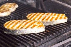 Cocinando los pescados asados a la parrilla Imagenes de archivo