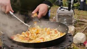 Cocinando verduras con la carne al aire libre verduras fritas en una caldera concepte de las vacaciones el humo sube lentamente s almacen de video