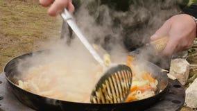 Cocinando verduras con la carne al aire libre verduras fritas en una caldera concepte de las vacaciones 4K almacen de video