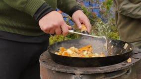 Cocinando verduras con la carne al aire libre Verduras fritas en una caldera Concepte de las vacaciones 4K metrajes