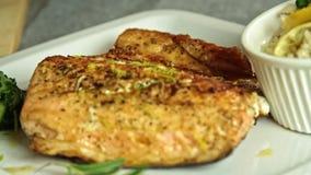 Cocinando y condimentando los pescados de color salmón con arroz y el pepino metrajes