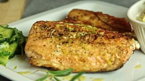 Cocinando y condimentando los pescados de color salmón con arroz y el pepino almacen de video
