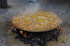 Cocinando y haciendo una paella española tradicional sobre el fuego abierto con madera y carbón del fuego Plato tradicional de Va imágenes de archivo libres de regalías
