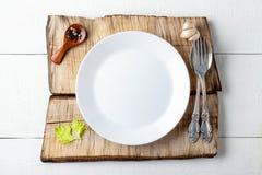 Cocinar concepto del fondo Placa, especia y cubiertos blancos vacíos foto de archivo libre de regalías