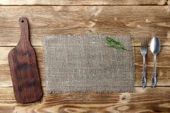 Cocinar concepto del fondo Tabla de cortar, harpillera y cubiertos del vintage Visión superior foto de archivo libre de regalías