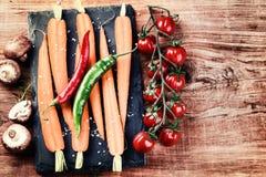 Cocinar el ajuste con las verduras orgánicas frescas en viejo backgr de madera Imagen de archivo libre de regalías