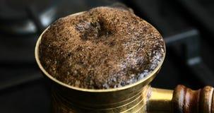 Cocinar el café turco en el cezve de cobre almacen de metraje de vídeo