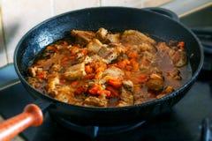 Cocinar el cerdo con la zanahoria en estufa Imágenes de archivo libres de regalías