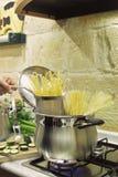 Cocinar el espagueti en un crisol del acero inoxidable fotos de archivo libres de regalías