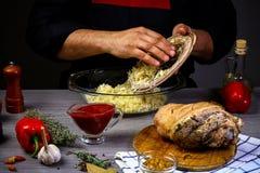 Cocinar el nudillo del cerdo con la cerveza, chucrut, salsa de chile por las manos del cocinero Concepto de la receta de la comid fotos de archivo