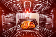 Cocinar el pollo en el horno Imagen de archivo libre de regalías
