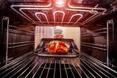 Cocinar el pollo en el horno Fotografía de archivo libre de regalías
