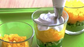 Cocinar el postre de crema en un vidrio, acodado con capas de frutas y de nueces el cocinero separa las capas fotografía de archivo