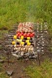 Cocinar kebabs y los tomates en los pinchos Fotos de archivo