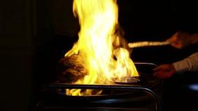 Cocinar la carne en el fuego, regando con el ajenjo y encender metrajes