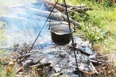 Cocinar la comida en caldera en el fuego de la leña en la comida campestre en verano foto de archivo