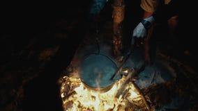 Cocinar la comida en una hoguera en bosque en la noche Vida del campo traveling almacen de video