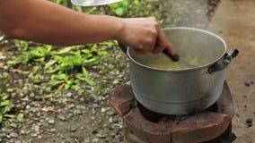 Cocinar la comida sobre el carbón de leña tradicional tailandés que quema la estufa vieja metrajes
