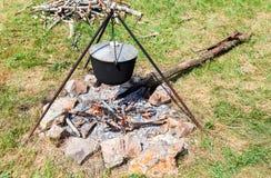 Cocinar la comida sobre un fuego abierto en el sitio para acampar en verano imágenes de archivo libres de regalías