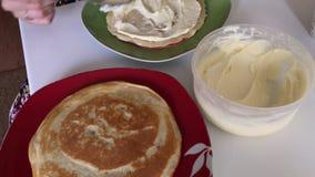 Cocinar la empanada con crema del mascarpone Una mujer lubrica las tortas del mascarpone y de la leche condensada almacen de video
