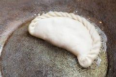 Cocinar la empanada en el sartén Fotos de archivo