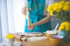 Cocinar la empanada Hogar acogedor La mujer está trabajando con la prueba, en las mentiras de la tabla un rodillo y una harina imagen de archivo