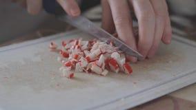 Cocinar la ensalada del cangrejo La mano femenina corta el cangrejo del ingrediente se pega con un cuchillo en el tablero Los día almacen de metraje de vídeo