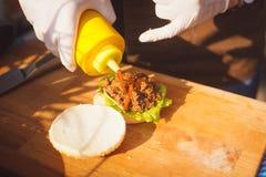 cocinar la hamburguesa con la salsa picante Imagen de archivo libre de regalías