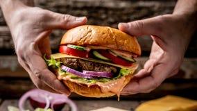 Cocinar la hamburguesa sabrosa por las manos del cocinero en la tabla de madera del vintage la comida se prepara en proceso menú imagen de archivo