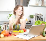 Cocinar a la mujer que mira el ordenador mientras que prepara la comida en kitche imagenes de archivo