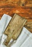 Cocinar a la tabla de cortar del Grunge en fondo de madera con la toalla de lino Fotos de archivo