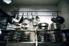 Cocinar las cacerolas y las herramientas colgado en una pared Fotografía de archivo libre de regalías