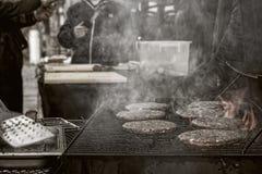 Cocinar las hamburguesas en una calle de la ciudad de la noche imágenes de archivo libres de regalías