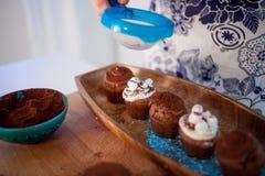 Cocinar las magdalenas, los molletes y una placa de los ingredientes para la decoración en la tabla imagen de archivo libre de regalías
