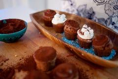 Cocinar las magdalenas, los molletes y una placa de los ingredientes para la decoración en la tabla Imagen de archivo