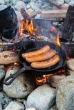 Cocinar las salchichas en sartén del arrabio en hoguera mientras que acampa Comida buena y positiva de la hoguera Fotografía de archivo