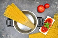 Cocinar los espaguetis en pote con los tomates Foto de archivo