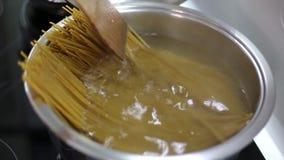 Cocinar los espaguetis en una cazuela con el agua hirvienda almacen de video