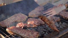 Cocinar los filetes de carne de vaca en una parrilla de la barbacoa metrajes