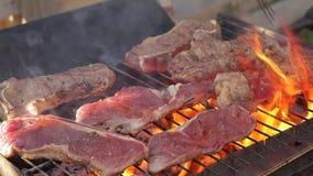 Cocinar los filetes de carne de vaca en una parrilla de la barbacoa almacen de video