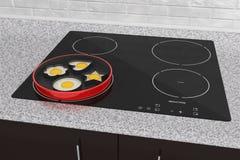 Cocinar los huevos en estufa del cooktop de la inducción Imagen de archivo