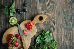 Cocinar los ingredientes para la ensalada de fruta en la tabla de madera fotos de archivo libres de regalías