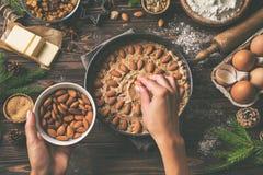 Cocinar los pasteles de la Navidad Adornamiento de las manos del ` s de la mujer joven festivo Imagen de archivo libre de regalías