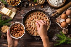 Cocinar los pasteles de la Navidad Adornamiento de las manos del ` s de la mujer joven festivo Foto de archivo