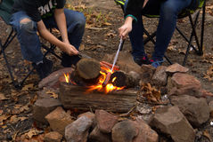 Cocinar los perritos calientes sobre el fuego abierto Imagenes de archivo