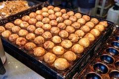 Cocinar Takoyaki que asa a la parrilla en la cacerola de acero, foo japonés tradicional imagenes de archivo